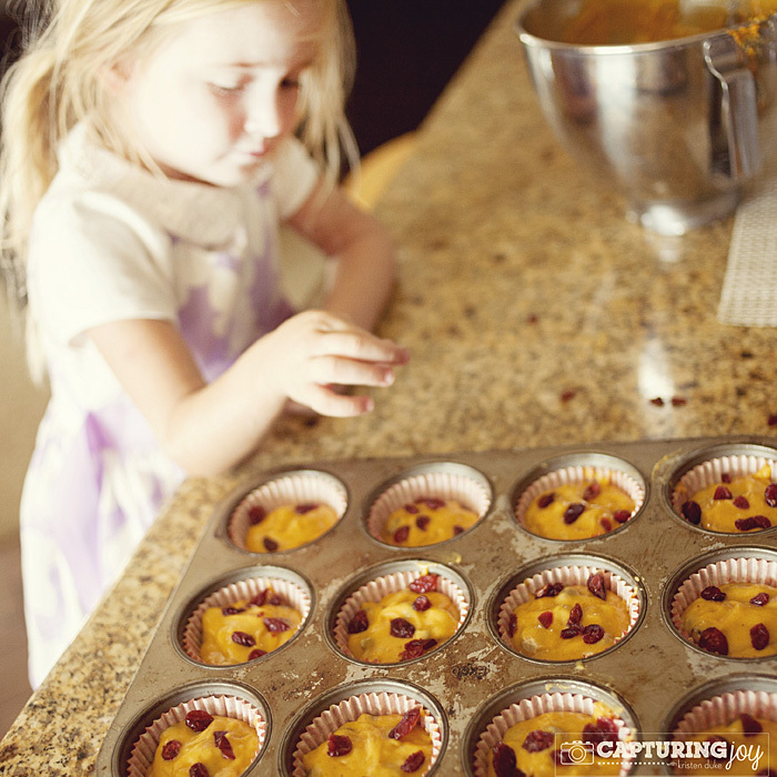 child adding cranberries to pumpkin cranberry muffins
