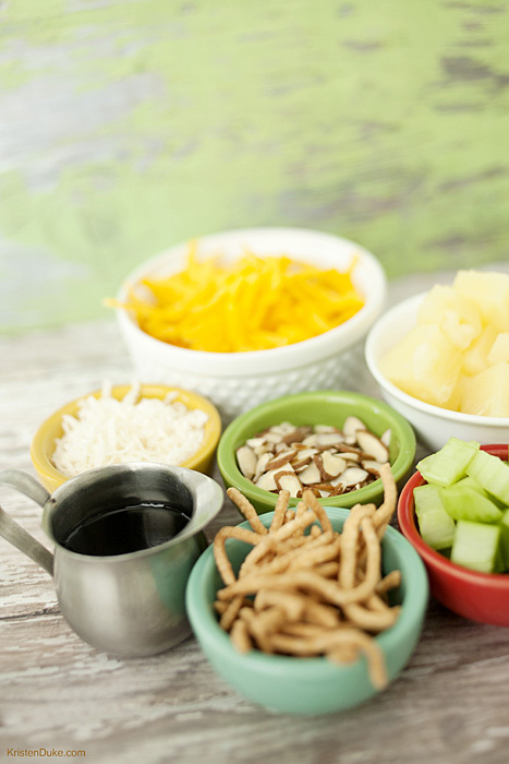 Hawaiian Haystack toppings, Hawaiian Haystacks recipe has a rice base, white sauce, cheese, pineapples, coconut, chow mein noodles, celery, almonds, cheese, and soy sauce. www.KristenDuke.com
