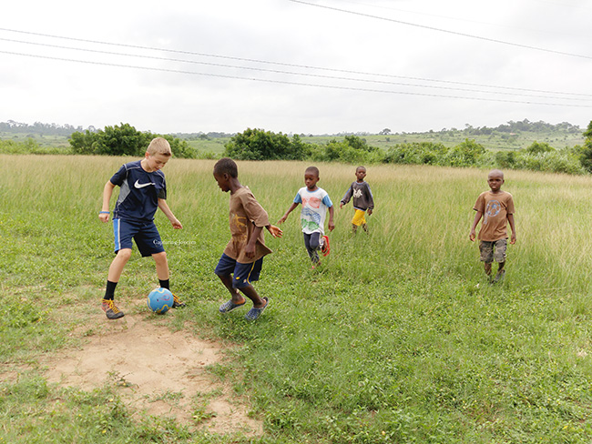 playging soccer futbol with kids in Ghana
