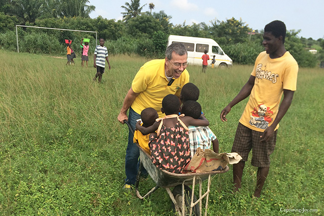 Mission President dad pushing wheelbarrow of Ghanaian kids