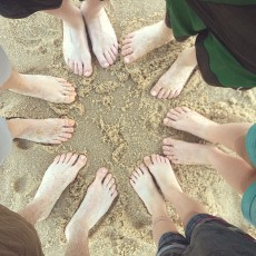 family feet in the sand