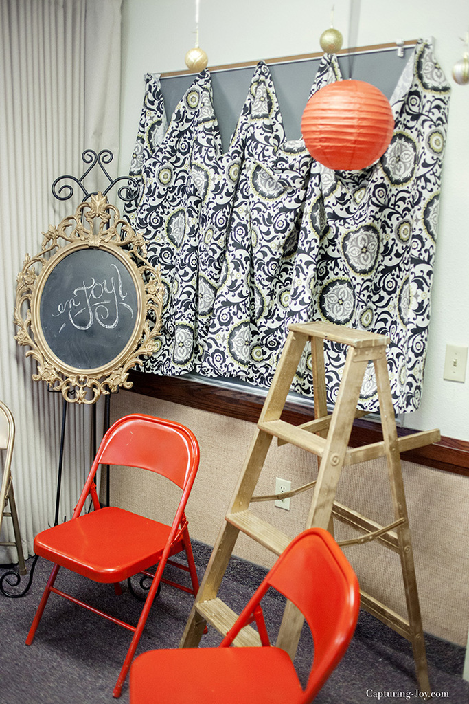 fabric covering a chalk board with painted metal chairs