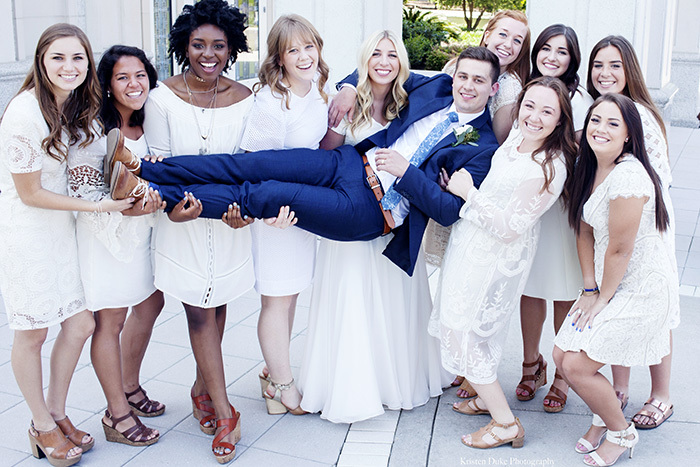 Bridesmaids holding groom in wedding pictures