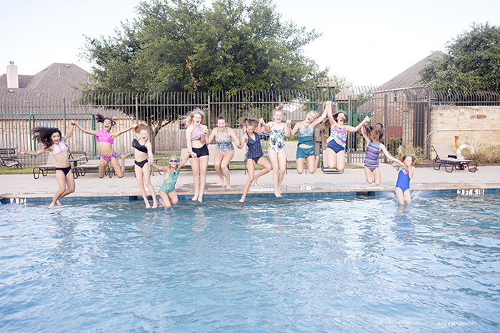 teen girls jumping into a pool