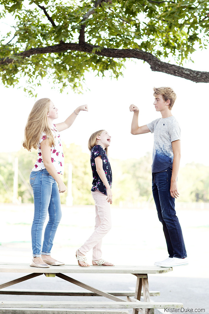 kids standing on picnic table in new clothes