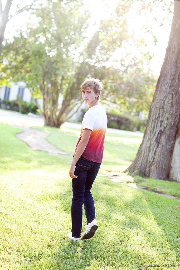 teen boy walking in grass